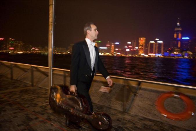 <strong>Saturday, February 16, 7:20PM:</strong> The lights of Victoria Harbor provide a picturesque backdrop for Principal Cello Carter Brey as he walks to the concert hall.