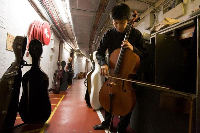 <strong>Friday, August 29, 2008, 8:30PM:</strong> New York Philharmonic cellist Wei Yu finds space backstage at Royal Albert Hall for some tuning during a break in the Orchestra's second concert at the BBC Proms in London.