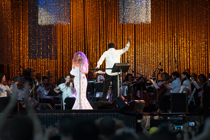 "<b>8:31PM:</b> Making a grand entrance from beneath the stage, pop diva Mariah Carey joins Alan Gilbert and the Orchestra for ""Looking In"" and ""My All."" Photo by Thomas Levinson/MLB Photos via Getty Images."