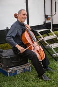 "<b>Prospect Park, July 11, 2013, 7:56PM:</b> The New York Philharmonic's 2013 Concerts in the Parks, Presented by Didi and Oscar Schafer, begin in Brooklyn's Prospect Park. Principal Cello Carter Brey — the summer's soloist — warms up behind the portable stage, which was built just that day. In its review of the performance, <em>The New York Times</em> described his account of Dvořák's Cello Concerto, led by Music Director Alan Gilbert, as ""probing, supple and, when called for, brilliant."" Photo by Stephanie Berger."