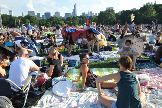 <b>Central Park, July 15, 2013, 6:40PM:</b> Despite the heat wave, more than 50,000 gathered on Central Park's Great Lawn for the Orchestra's free performance. These fans have arrived early to stake out a good spot, enjoy a picnic, and even devise a shaded shelter before the downbeat. Photo by Stephanie Berger.