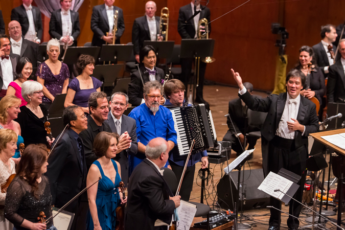 <b>8:22PM:</b> After a triumphant performance of Osvaldo Golijov's <em>Azul,</em> the Orchestra and Music Director Alan Gilbert take their bows with cellist Yo-Yo Ma, percussionist Jamey Haddad, Mr. Golijov himself, percussionist Cyro Baptista, and hyper-accordionist Michael Ward-Bergeman. Photo by Chris Lee.