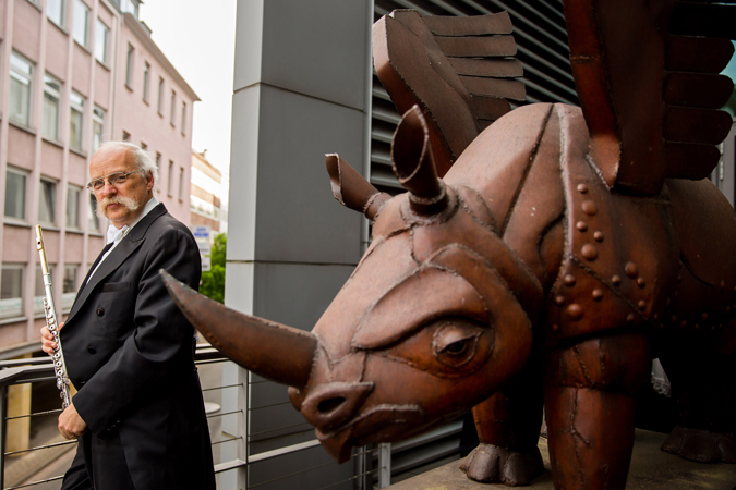 <b>Dortmund, May 9, 2013, 5:30PM:</b> One week into the EUROPE / SPRING 2013 tour, the Philharmonic stops in Dortmund, Germany. Before the evening's concert at Konzerthaus Dortmund, Principal Flute Robert Langevin greets a flying rhino, ubiquitous in the city. The Konzerthaus picked the rhino as a mascot for its sensitive ears (it can move them a full 360 degrees and can hear sounds humans can't), and added wings to symbolize both Dortmund's imperial history and the sound of music being carried from the Konzerthaus. <br>All photos by Chris Lee