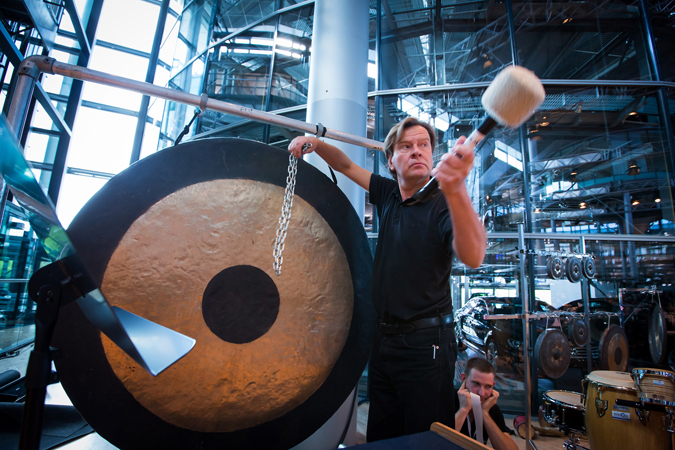 <b>Dresden, May 13, 2013, 10:20AM:</b> At rehearsal, the composer himself strikes a large Chinese tam-tam with a chain from the Volkswagen factory. Repurposing found objects recovered at or near the performance site is a composer-mandated requirement for any performance of <i>Kraft.</i>