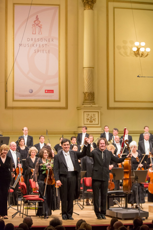 "<b>Dresden, May 13, 2013, 9:10PM:</b> Jan Vogler, Alan Gilbert, and the Orchestra take a bow. ""I was about nine when my father's friend brought a record to our home of Leonard Rose, former Principal Cello of the New York Philharmonic, performing Bloch's <i>Schelomo,</i>"" Mr. Vogler has said. ""I became a cellist partly because of Leonard Rose and partly because of <i>Schelomo.</i>"""