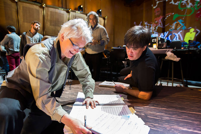 "<b>11:39AM:</b> Meanwhile, onstage, Music Director Alan Gilbert confers with Associate Principal Oboe Sherry Sylar while the production's assistant conductor, Grant Sturiale, looks on. ""My favorite program with Alan so far may be the <em>Sweeney Todd</em> performances!"" Sherry Sylar says. ""I am lucky to sit right next to the barber chair (so close it feels like I am in an episode of <em>Dexter</em> — complete with blood splatter on me!). When Bryn Terfel sings with his elegant, rich voice, my whole being vibrates! And to be so close to the comedic timing genius of Emma Thompson is beyond exciting! I only wish I could look up more as I <em>am</em> a bit busy playing."""