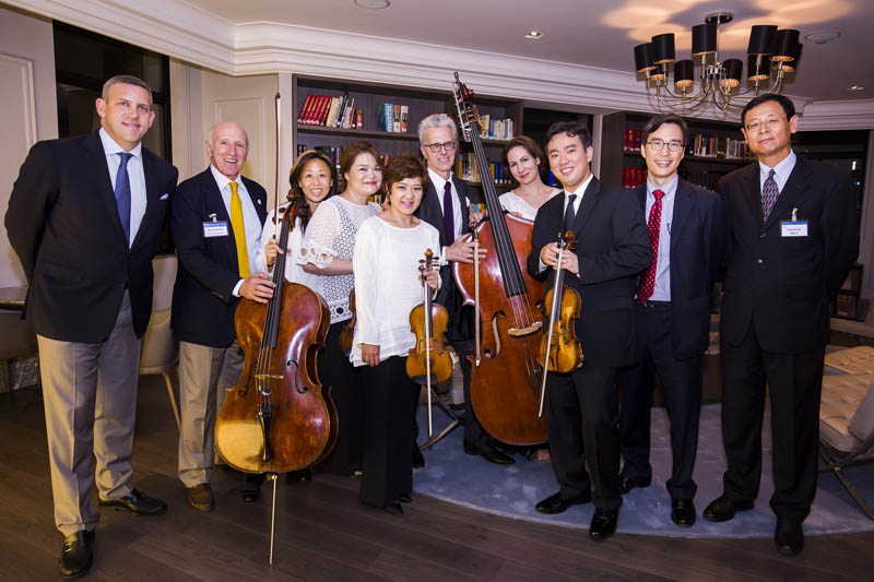 "<b>Shanghai, July 6, 2016, 7:43PM:</b> That evening Philharmonic musicians perform chamber versions of Vivaldi's <em>The Four Seasons</em> and ""The Star-Spangled Banner"" at Jones Day Shanghai, celebrating the Fourth of July with American food, classical music, drinks, and merriment. Here Philharmonic President Matthew VanBesien and Chairman Oscar S. Schafer pose with the musicians who performed — Associate Principal Cello Eileen Moon; Assistant Concertmaster Michelle Kim; Acting Principal, Second Violin Group, Lisa Kim; Principal Bass Timothy Cobb; Associate Principal Viola Rebecca Young; and Concertmaster Frank Huang — and Jones Day Shanghai Partner-in-Charge Peter J. Wang and Of Counsel Patrick H. Hu."