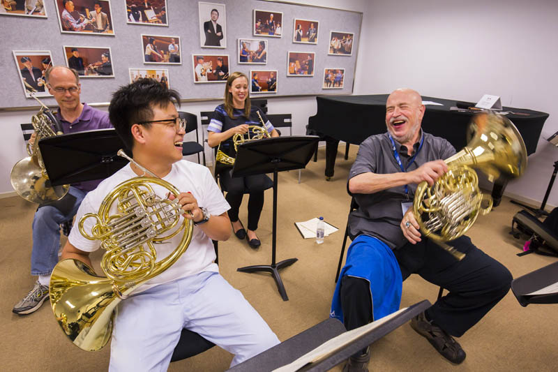 <b>Shanghai, July 7, 2016, 2:29PM:</b> Down the hall, Principal Horn Philip Myers and hornists Leelanee Sterrett and R. Allen Spanjer share a laugh with an SOA student as they work on orchestral repertoire.