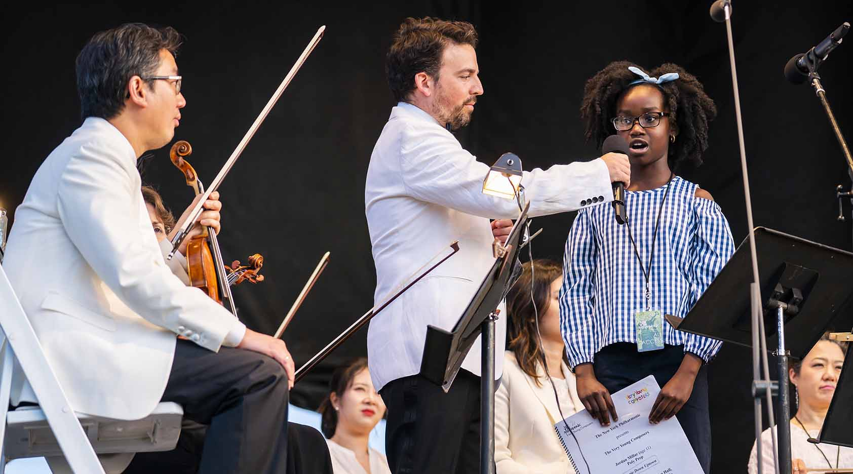 New York Philharmonic Very Young Composer Jordan Millar being interviewed onstage at a Concerts in the Parks concert in 2018