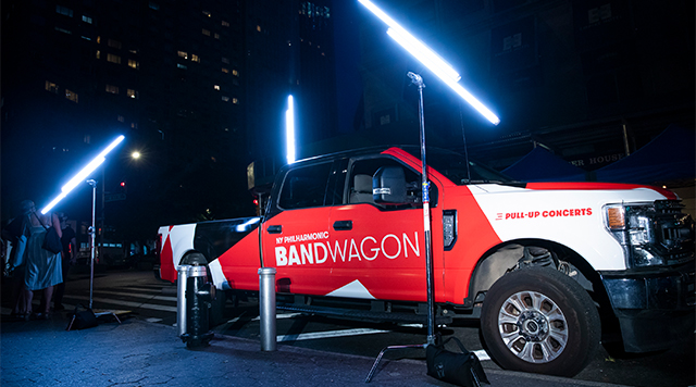 A red and white pickup truck labeled Bandwagon on the side door